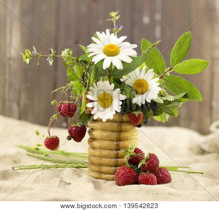 Seasonal still life with summer flowers and strawberries