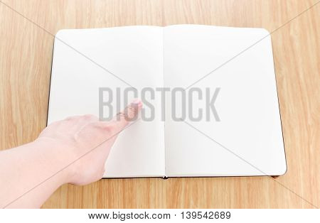 Hand Pointing On Blank Open Notebook Lay It On Wooden Table,template Mock Up For Adding Your Text