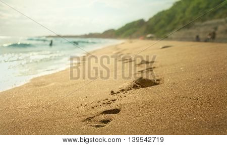 Foot prints in sand on beach by sea on sunny day.