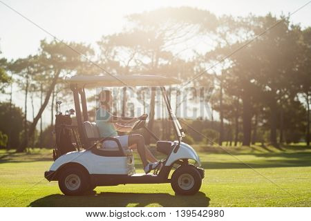 Side view of man sitting in golf buggy on sunny day