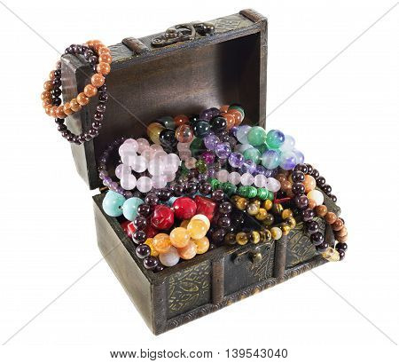 Wooden chest with treasures isolated on white