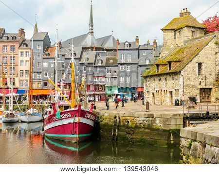 HONFLEUR FRANCE - MAY 6, 2014: Old boat and medieval Lieutenancy building - entrance to the old harbour. Honfleur, Normandy, France