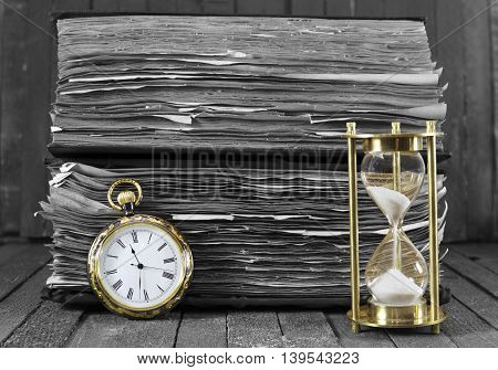 Still life with pocket watch and sand clock on wooden background, black and white style