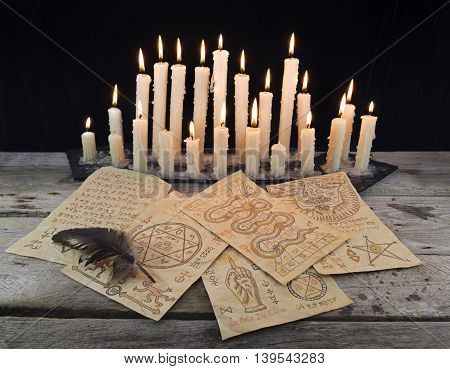 Magic papers with candles and quill on old wooden table, Halloween background