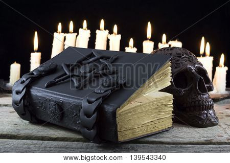 Magic book with burning candles and skull
