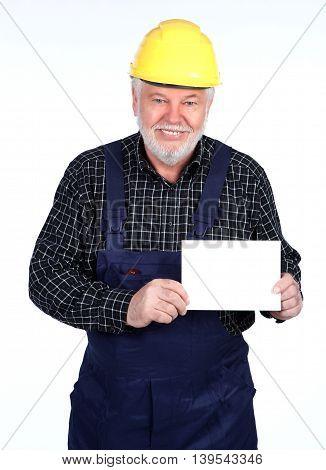 Smiling senior craftsmen with helmet shows withe sign