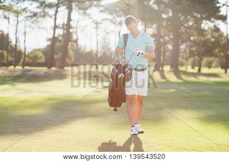 Young man looking at golf club while standing on field
