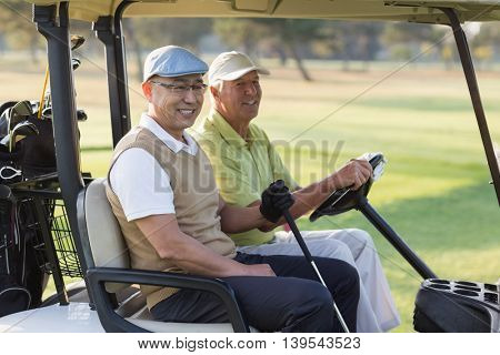 Smiling male golfer friends sitting in golf buggy on sunny day