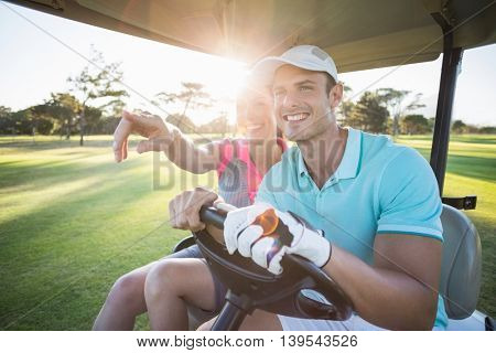 Smiling golfer woman pointing by man while sitting in golf buggy on sunny day