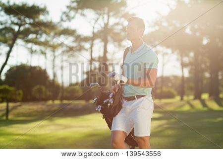 Young man carrying golf bag while standing on field