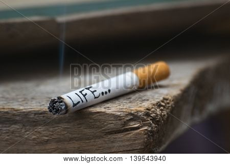 Burning cigarrete with smoke and written word life on wooden surface. Represents concept of