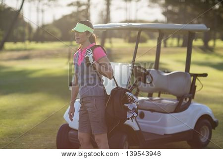 Woman standing by golf buggy on field