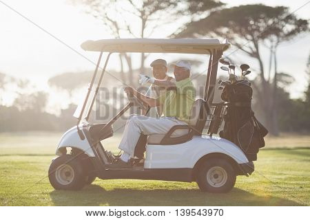 Mature golfer man pointing while sitting by friend in golf buggy on field
