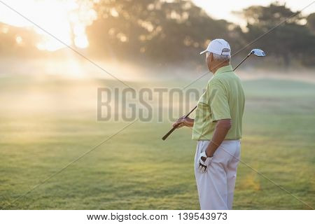Mature golfer man standing on field during sunny day