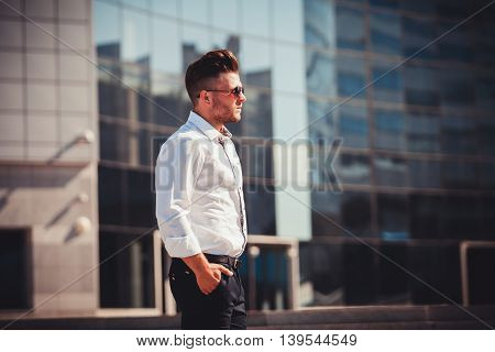 serious successful man in shirt and glasses stands near the business center