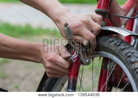man repairs a bike in the summer outdoors