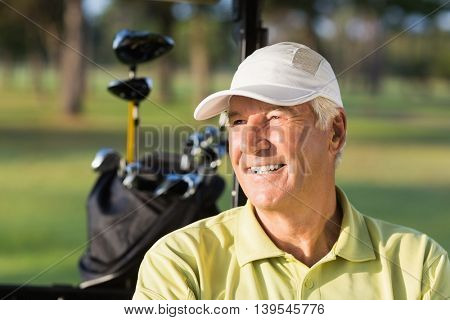 Close-up of smiling golfer man sitting in golf buggy
