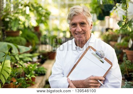 Portrait of male scientist holding clipboard while standing at greenhouse