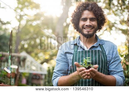 Low angle portrait of happy male gardener holding sapling at greenhouse