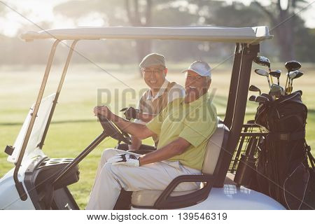 Portrait of cheerful golfer friends sitting in golf buggy on sunny day