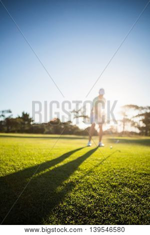 Full length of man playing golf on field against clear sy