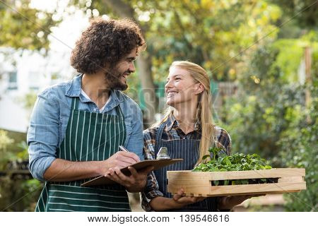 Female gardener holding plants in crate while man writing on clipboard outside greenhouse