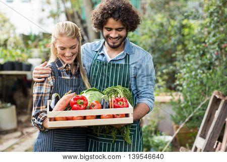 Portrait of smiling couple holding vegetables crate outside greenhouse