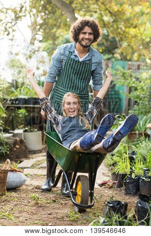 Portrait of cheerful man giving wheelbarrow ride to female gardener outside greenhouse