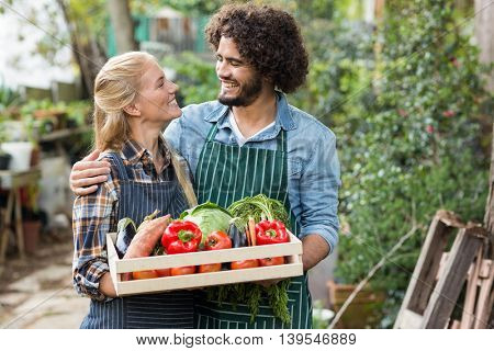 Smiling couple looking at each other while holding vegetables crate outside greenhouse