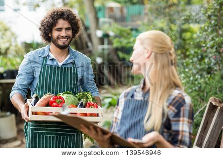 Happy male gardener looking at woman while holding vegetable crate outside greenhouse