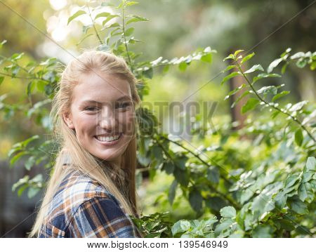 Portrait of happy female gardener standing by plants at greenhouse