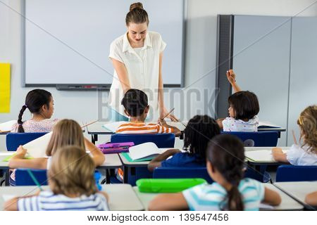 Female teacher teaching children in classroom