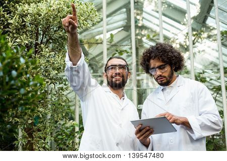 Male scientist pointing while colleague using digital tablet against greenhouse