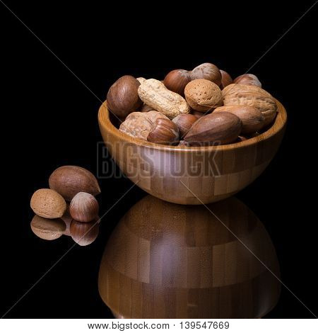 Nuts in wooden bowl. Bulrap and green background.