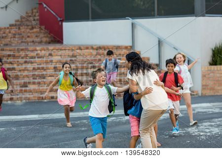 Happy children running towards teacher outside school