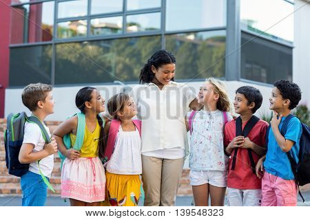 Cheerful female teacher with children standing outside school