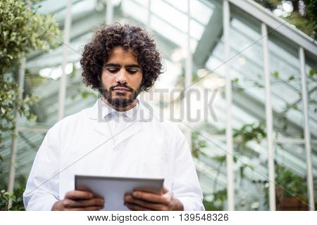 Low angle view of male scientist using digital tablet outside greenhouse