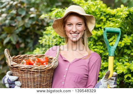Portrait of happy female gardener holding tomato basket and work tool at greenhouse