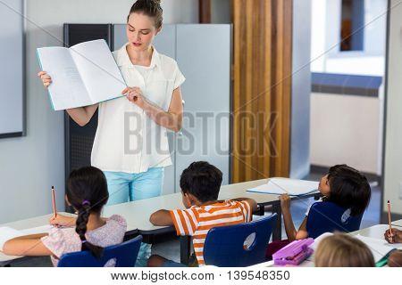 Female teacher showing book to schoolchildren in classroom