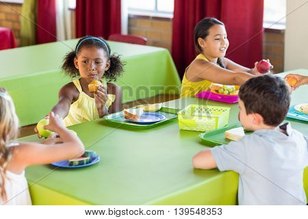 Schoolchildren having breakfast in canteen
