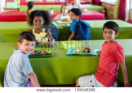 Portrait of cute schoolchildren having meal in canteen