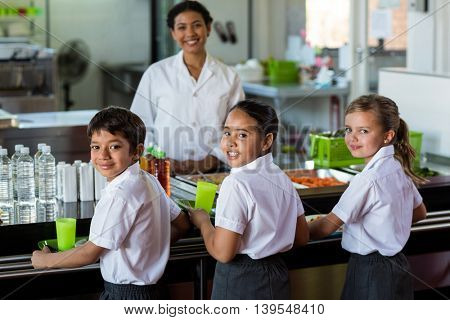 Portrait of smiling woman with schoolchildren in canteen