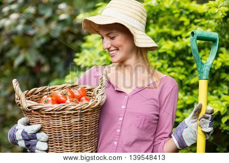 Happy female gardener holding tomato basket and work tool at greenhouse