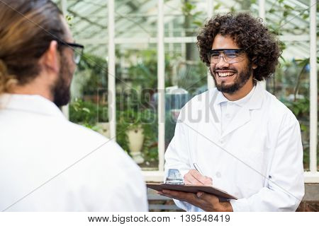 Male scientists smiling while discussing outside greenhouse