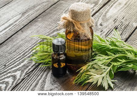 Essential oil tincture of wormwood (Artemisia absinthium) in a pharmaceutical brown bottles fresh sagebrush branches on a dark wooden table