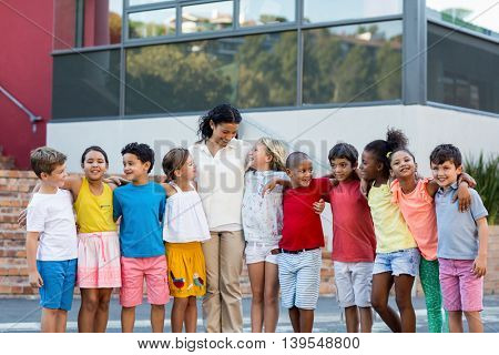 Happy female teacher with children standing outside school