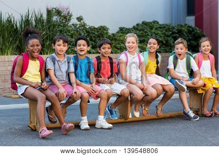 Portrait of smiling schoolchildren on seat outside school