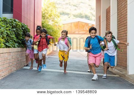 Portrait of happy schoolchildren running on footpath