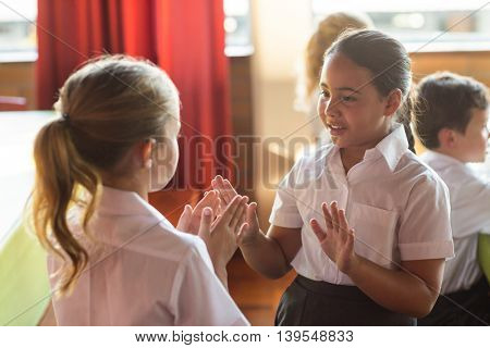 Cute girls playing clapping game in school canteen