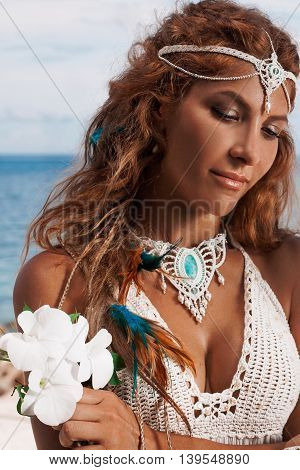 young bride in white dress on beach